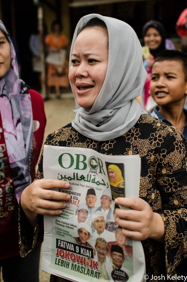 A woman holds a copy of a prominent Muslim publication which endorsed Jokowi