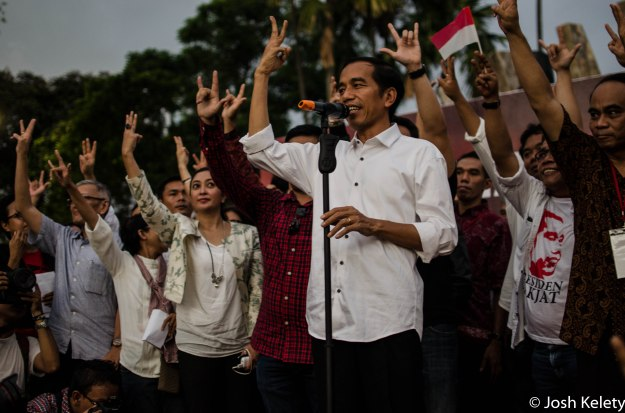 Jokowi and supporters hold up three fingers to symbolize unity in wake of election decisiveness.