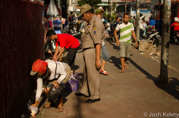 Saptol-PP officer watches street vendors vacate the premises