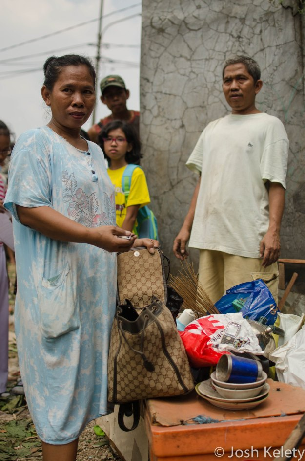 A Mampang resident of 27 years stands in front of her belongings on the remains of her former home. She said no one from the city government informed her of the evictions.