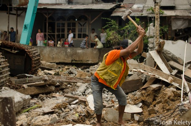 A city worker helps demolish a home along the Mampang river while local residents look on