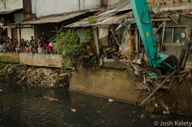 A city excavator demolishes homes along the Mampang river